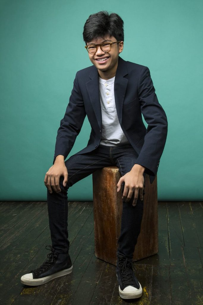 Joey Alexander sat down in front of green background